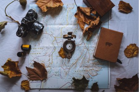 Map with leaves, journal, camera, and compass on top.